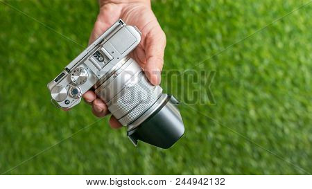 Hand Holding A Camera - Close Up Of Photographer Hand Holding A Camera On Green Grass Background. Cl