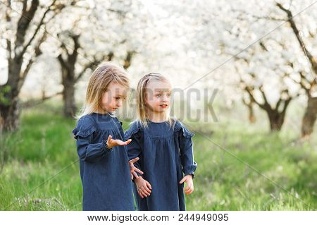 Happy Twin Sisters Children. Girls Sister In A Park At A Picnic Laugh, Smile.