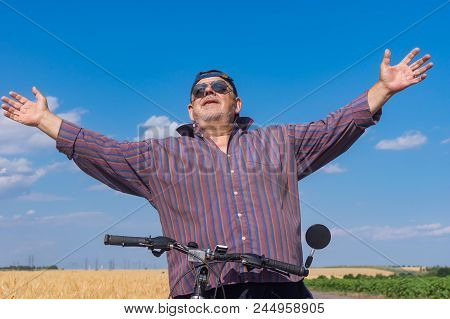 Outdoor Portrait Of A Bearded, Chubby Senior Man Being Happy To Ride On A Bicycle