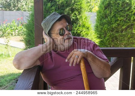 Portrait Of Bearded Senior Man In Sunglasses Resting While Sitting On Veranda At Summer Season