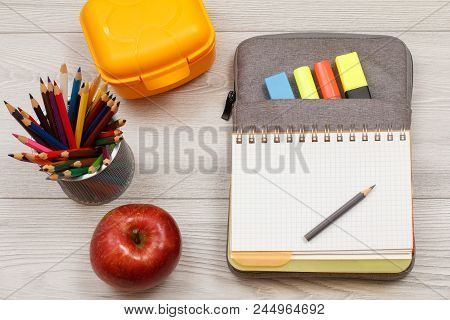 School Supplies. Apple, Metal Stand For Pencils With Color Pencils, Yellow Sandwich Box, Open Exerci
