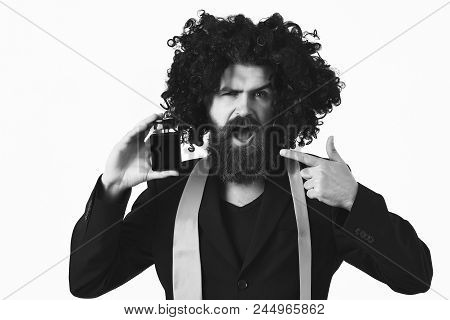 Caucasian In Suit And Black Curly Wig Holding Perfume. Bearded Man, Long Beard. Brutal Caucasian Hip
