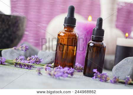 bottle of aromatherapy lavender oil with lavender flowers - beauty treatment