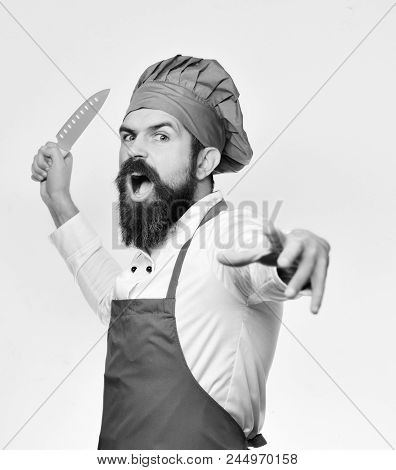 Cook with angry face in burgundy apron and chef hat. Chef pretends to throw sharp blue knife. Cooking and professional culinary concept. Man with beard in cook uniform isolated on white background. poster