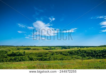 Green Nature Landscape With Grassland Hills And Blue Sky, Tranquil Countryside View