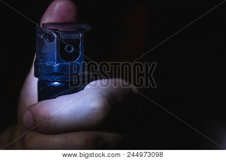 A Man's Hand Holds A Gas Pepper Spray In The Dark, A Black Backg