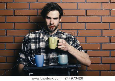 Guy Holding Cup On Brick Wall Background. Sportive Handsome Bearded Guy In Black And White Checkered