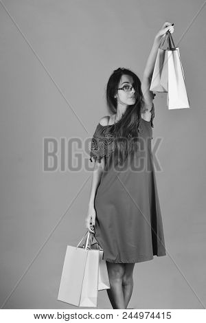 Girl Stands On Red Background Holding Pink Shopping Bags Up. Woman Wears Fashionable Dress. Shopping
