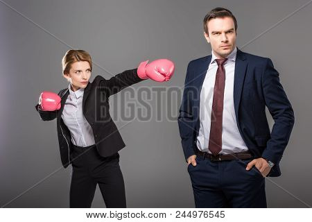 Confident Businesswoman In Boxing Gloves And Handsome Businessman, Isolated On Grey, Feminism Concep