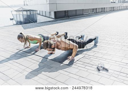 Fit fitness woman and man doing fitness exercises outdoor at city background. Couple doing hamstring leg exercise and stretches. Female amd male sports models exercising in summer at morning. poster