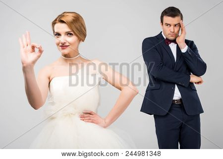 Bride In Wedding Dress Showing Ok Sign While Worried Groom Standing Behind, Isolated On Grey, Femini