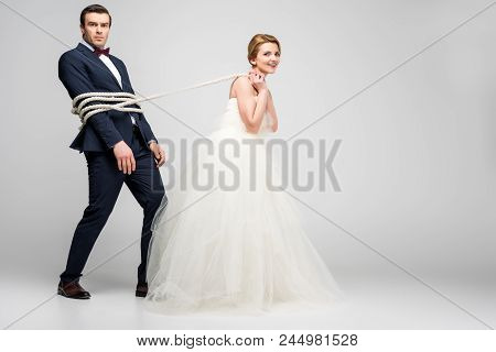 Beautiful Bride Pulling Groom Bound With Rope, Isolated On Grey, Feminism Concept