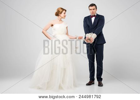 Bride In Wedding Dress And Groom Bound With Rope, Isolated On Grey, Feminism Concept