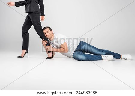 Husband Holding Leg Of His Business Wife, Feminism Concept, Isolated On Grey
