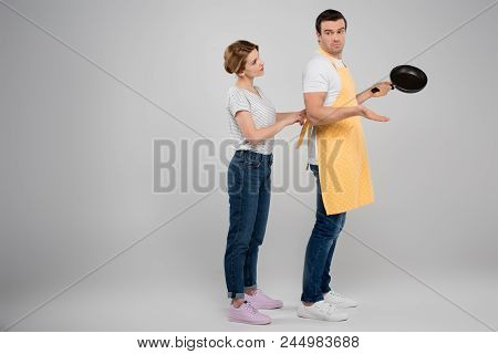 Wife And Husband In Apron With Frying Pan, Feminism Concept, Isolated On Grey