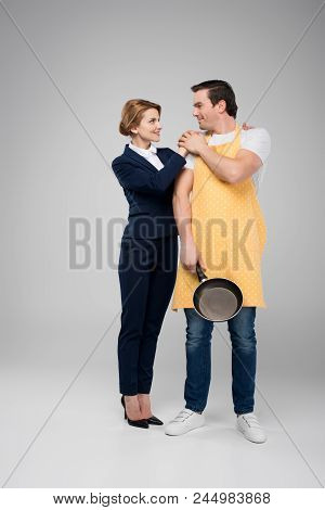 Businesswoman And Male Householder Standing Together With Frying Pan, Feminism Concept, Isolated On