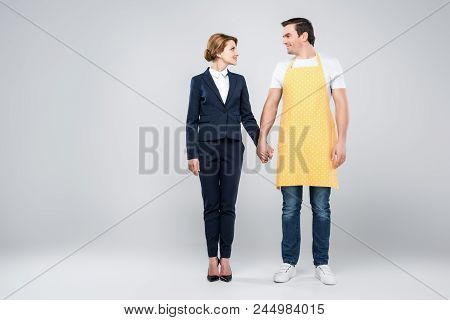 Businesswoman In Suit And Male Householder Holding Hands, Feminism Concept, Isolated On Grey