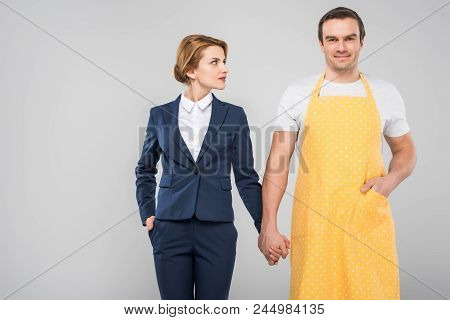 Businesswoman And Male Householder Holding Hands, Feminism Concept, Isolated On Grey