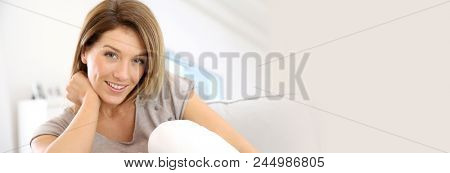 Attractive blond woman relaxing in sofa at home, template