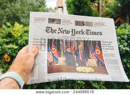 Paris, France - June 13, 2018: Man Reading The New York Times Newspaper  Showing On Cover  U.s. Pres