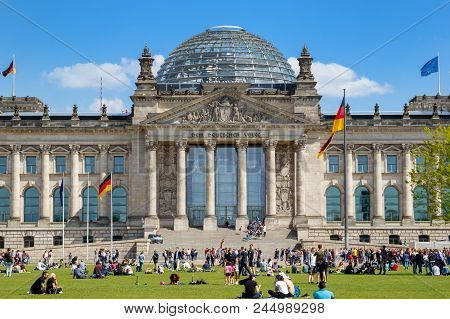 Berlin, Germany - Apr 28, 2018: People Relaxing On The Grass In Front Of The Reichstag Building, Sea