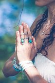 close up of yoga woman hands in namaste gesture with lot of boho style jewelry rings and bracelets outdoor summer day poster