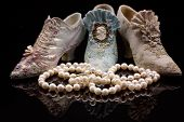 A string of lustrous creamy pearls in front of three ornately decorated old fashioned miniature shoes on a black surface with reflections poster