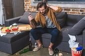 loner with hangover looking at bottle of wine at living room poster