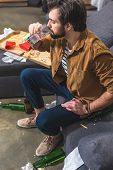 high angle view of loner drinking water and having hangover at living room poster