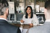 Business, career and placement concept - young asian woman smiling and holding resume, while sitting in front of directors during corporate meeting or job interview poster