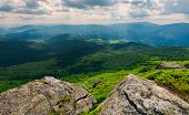 rocks on the edge of a  mountain. location Pikui mountain. Runa mountain in the far distance. Beautiful summer landscape of Carpathian mountains on a cloudy day poster