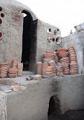 Preparing clay pottery for firing in adobe furnace. Traditional moroccan berber craft, Fez, Morocco, North Africa poster