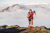 Runner trail running fitness man on endurance run - motivation and concentration on race in sky and clouds background on nature landscape. Focused athlete with backpack and hairband training cardio. poster