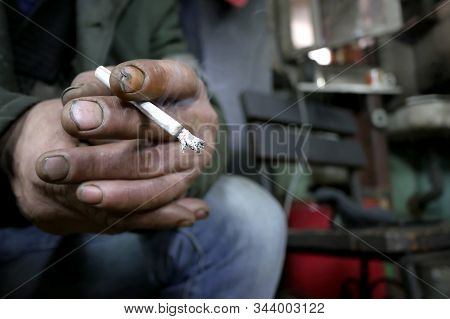 Dirty Unkempt Hands Of A Man With A Cigarette