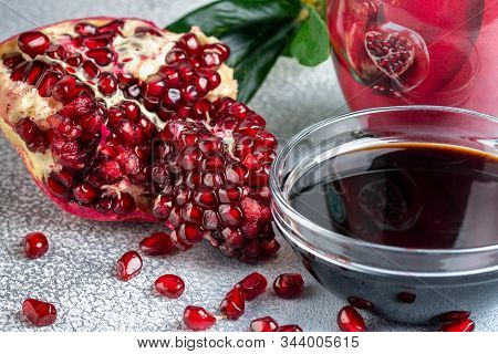 Narsharab. Saucer With Pomegranate Sauce With Fresh Ripe Pomegranate Fruits With Leaves On A Light R