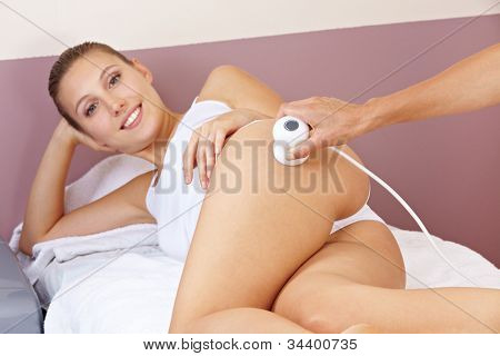 Woman getting skin tightening through electrical stimulation in spa