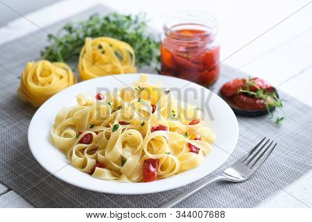 Italian Traditional Pasta Tagliatelle With Dried Tomatoes And Thyme On A Light Background.