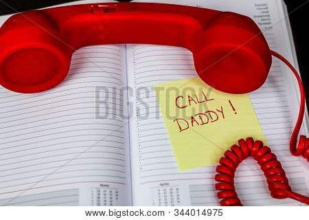 Writing Call Daddy On Memo Post Reminder.  Sticky Paper With Text Call Daddy And Landline Phone.