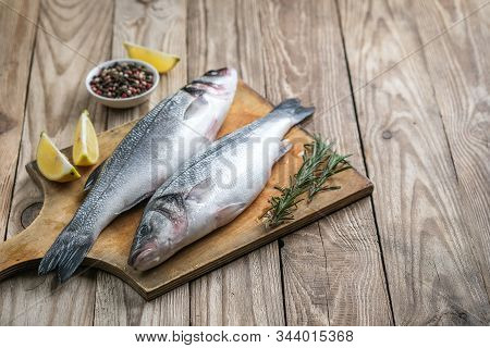 Fresh Seabass And Ingredients For Cooking. Raw Fish Seabass With Lemon, Spices And Herbs On Wooden R