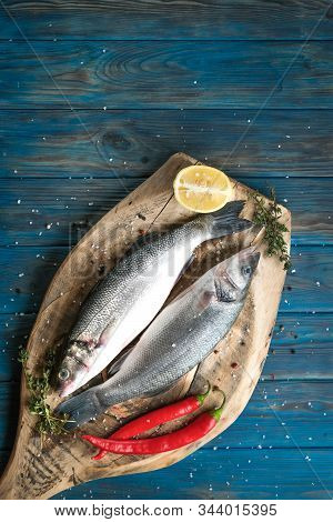 Fresh Seabass And Ingredients For Cooking. Raw Fish Seabass With Lemon, Spices And Herbs On Bluerust