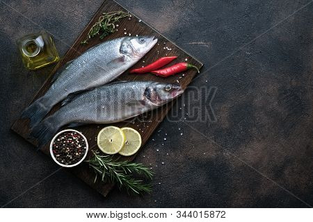 Fresh Seabass And Ingredients For Cooking. Raw Fish Seabass With Lemon, Spices And Herbs On Black Ru