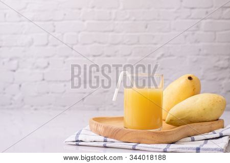 Kitchen Table With Mangoes Juice And Fruit.