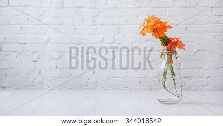 Glass Vase With Orange Beautiful Flower On White Table.