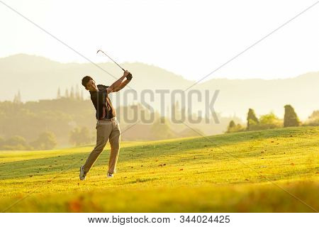 Professional Golfer Asian Man Swing And Hitting Golf Ball Practice At Golf Driving Range And Fairway