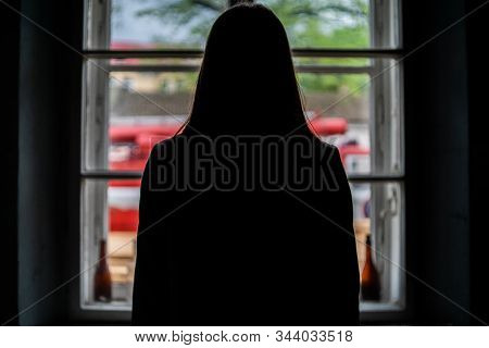 A Silhouette Of A Woman Looking Out The Window With A View Of The Nature. Someone Was Standing By Th