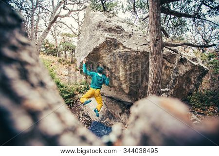 Athletic Man Climbing Hard Boulder Problem In Forest. Sport Climbing, Bouldering. Outdoor. Top View