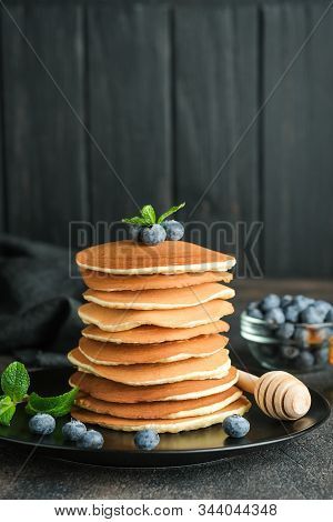 Delicious Pancakes, With Fresh Blueberries, Strawberries And Caramel On A Dark Background.