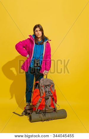 Looks Sad, Unhappy. Portrait Of A Cheerful Young Caucasian Tourist Girl With Bag And Binoculars Isol