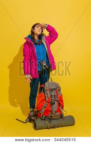 Looking Up, Dreamful. Portrait Of A Cheerful Young Caucasian Tourist Girl With Bag And Binoculars Is