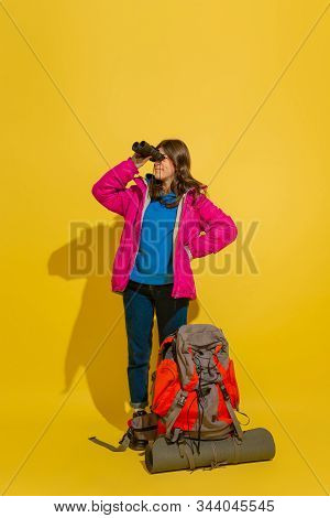Looking Far Forward. Portrait Of A Cheerful Young Caucasian Tourist Girl With Bag And Binoculars Iso